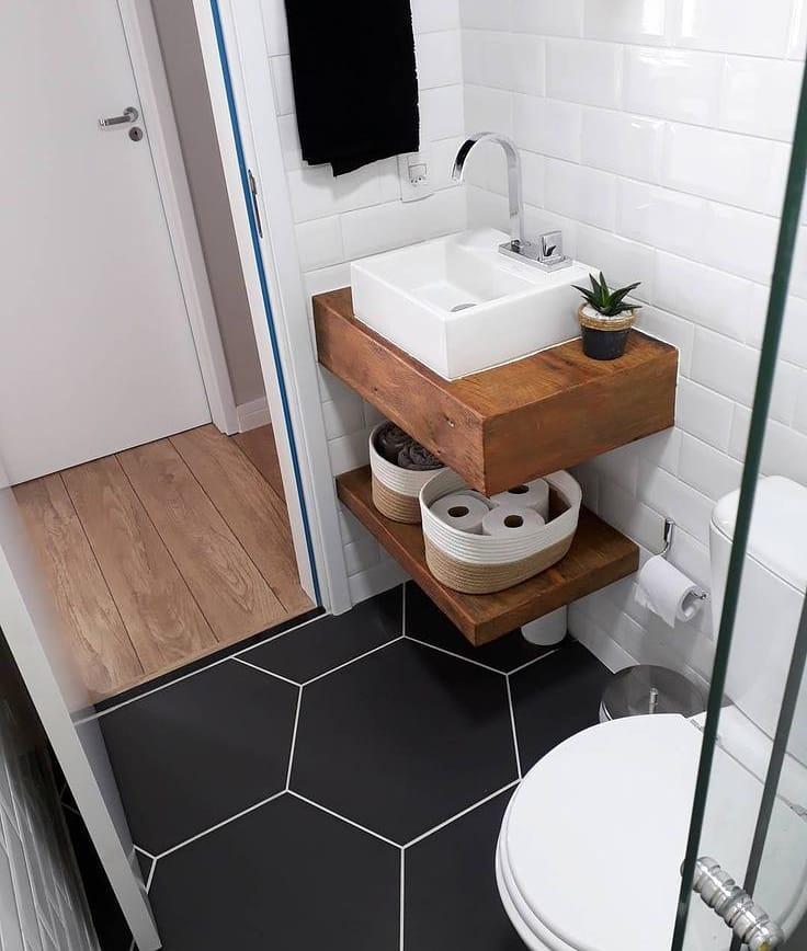 banheiro pequeno estilo escandinavo com piso hexagonal preto e azulejo de metro