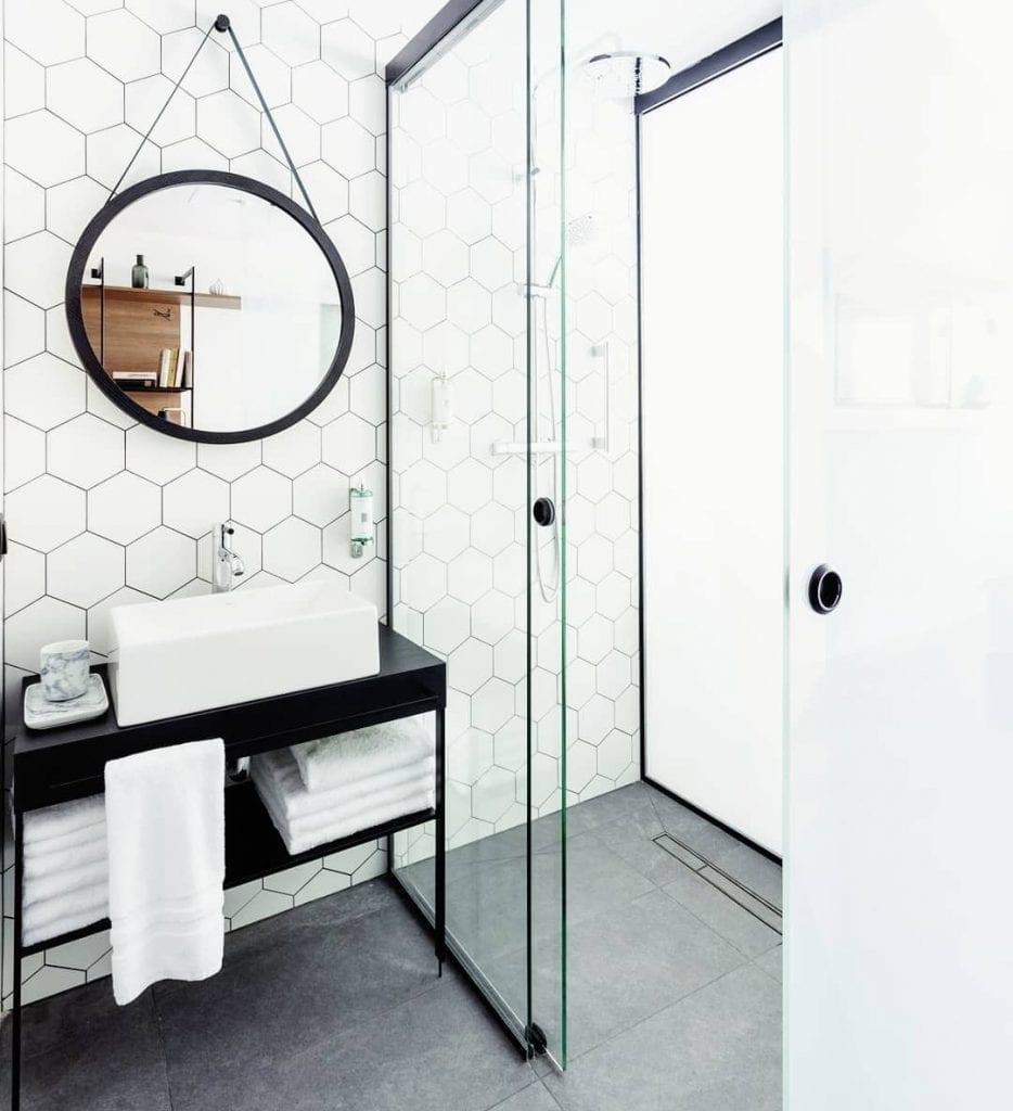 banheiro estilo escandinavo com pastilha hexagonal na parede e detalhes em preto