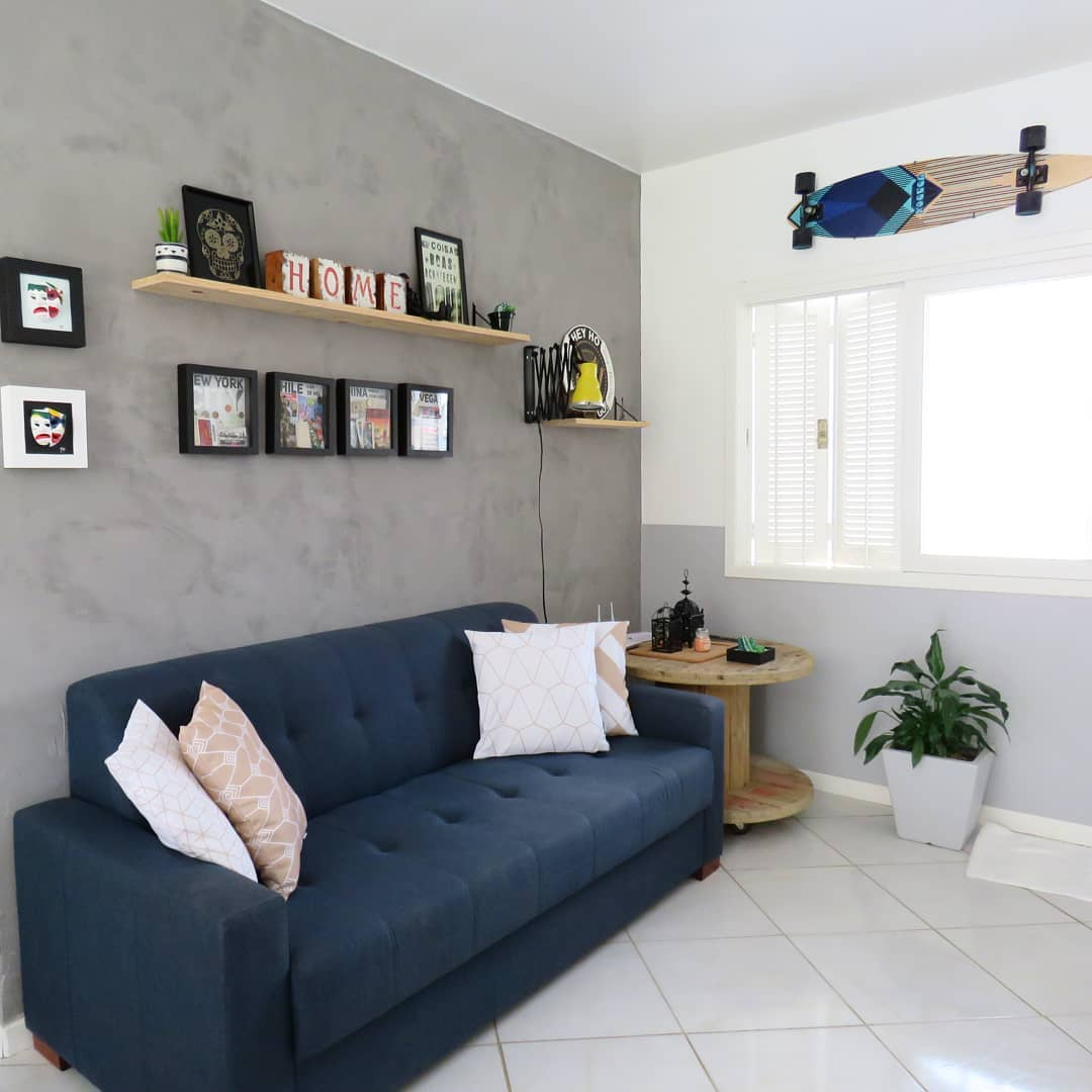 sofa azul marinho em decoração moderna com parede de cimento queimado