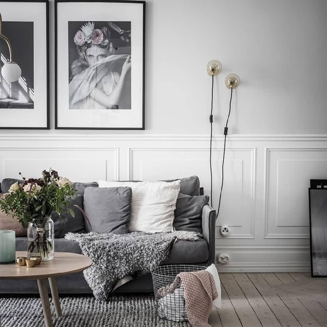 ambiente aconchegante com sofa cinza e paredes em boiserie