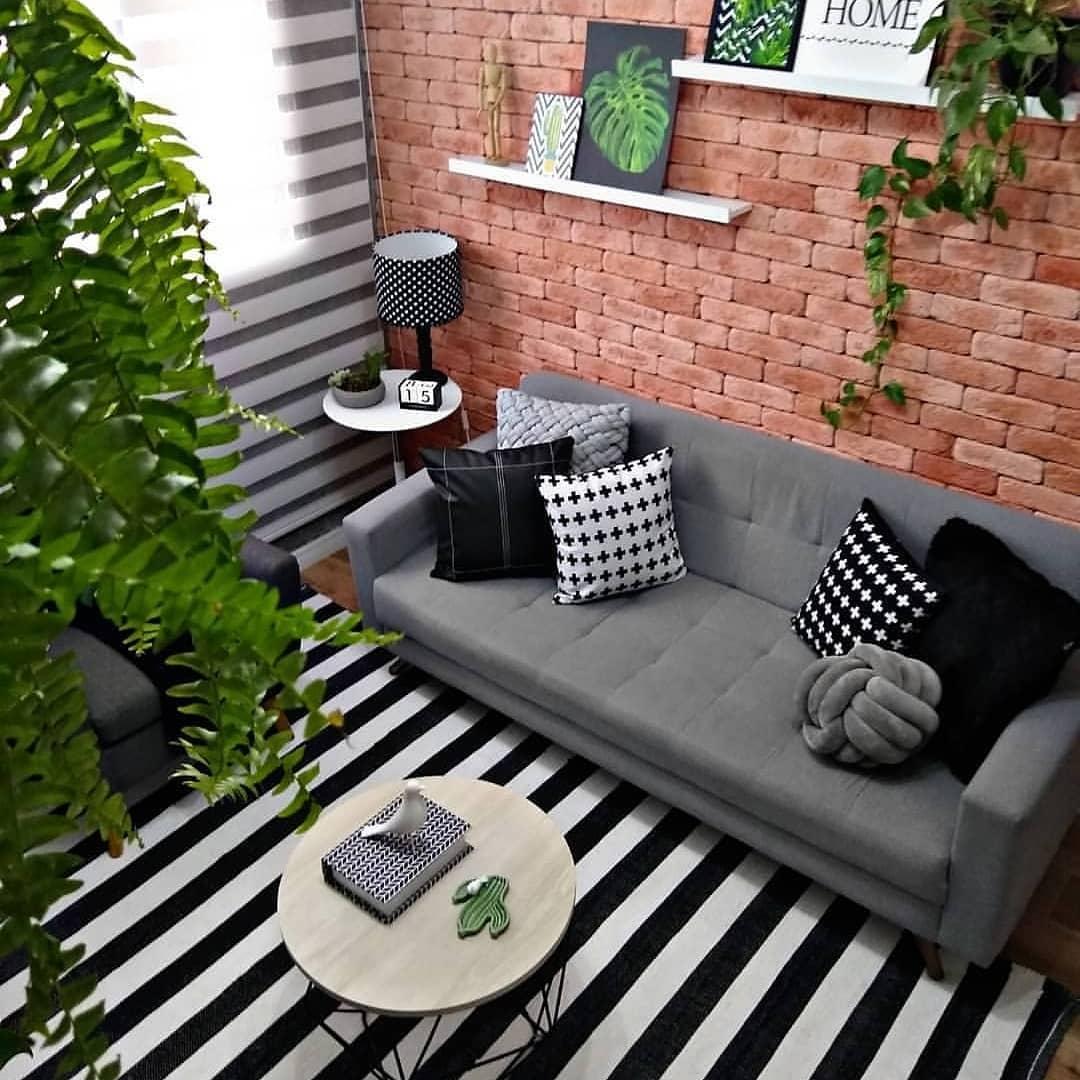 sofa cinza em parede de tijolinhos