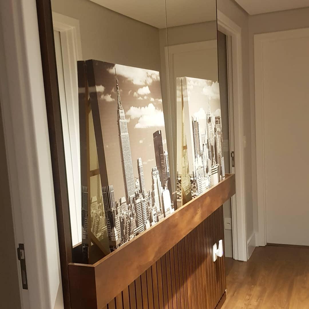 decoração de corredor com espelho e quadros