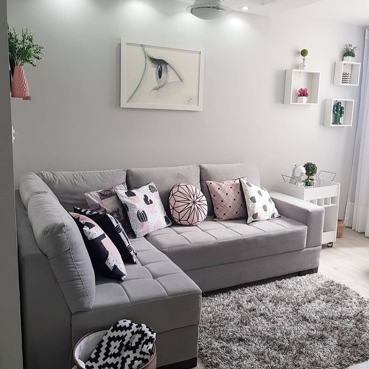 sofa cinza de canto em apartamento feminino