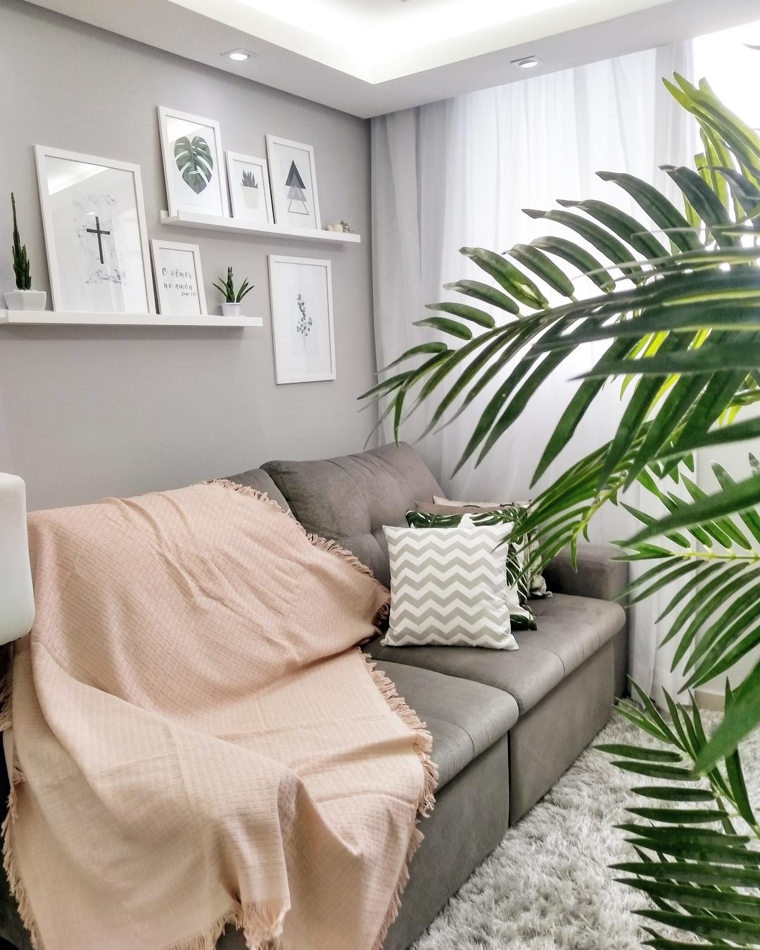 sofa cinza pequeno com manta rosa e quadros decorativos