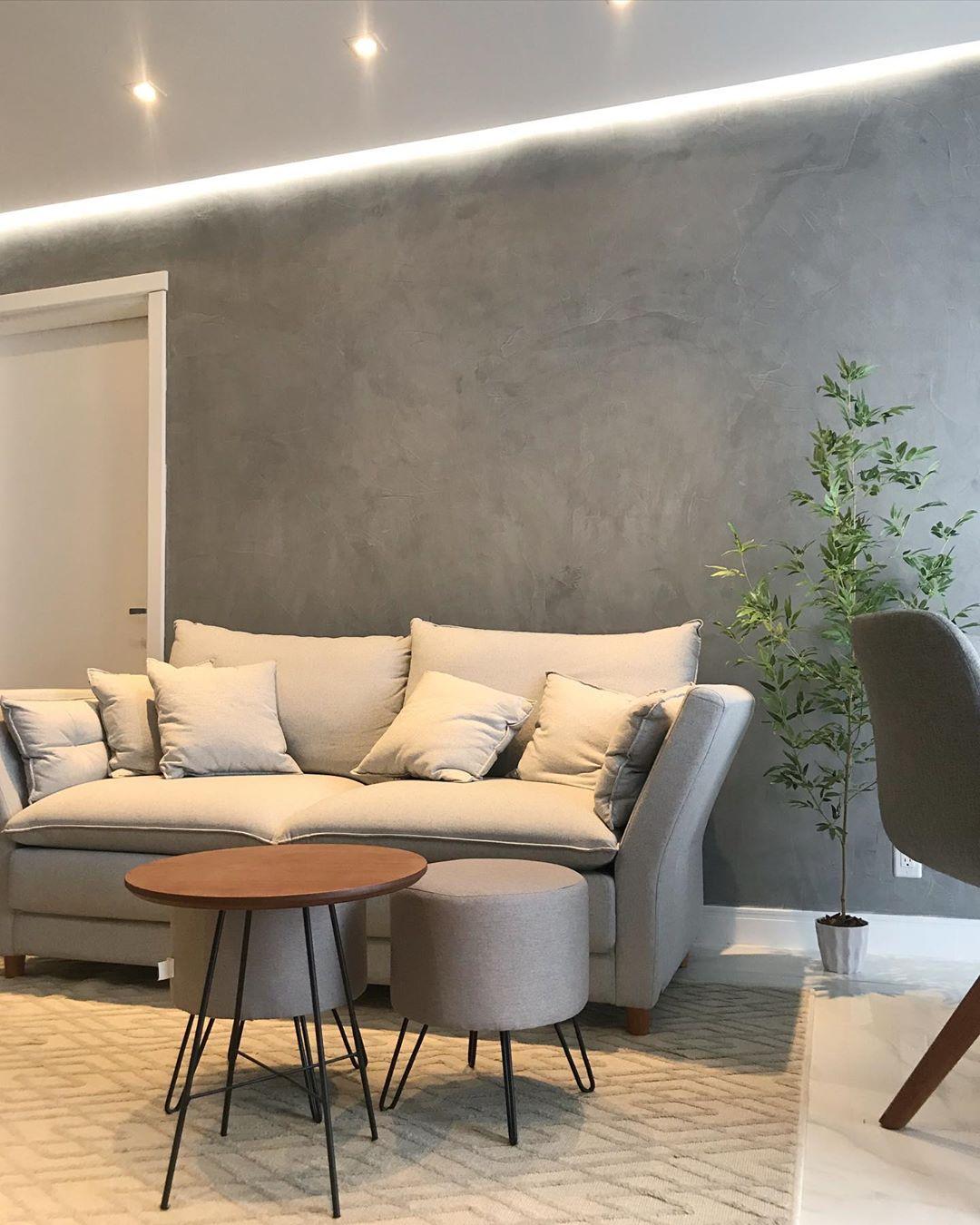 sofa cinza e parede de cimento queimado