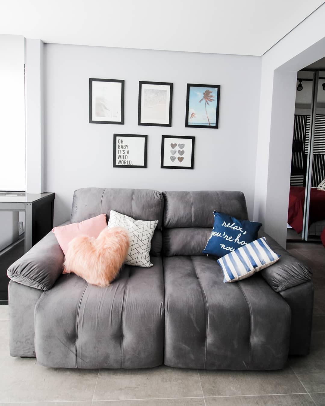 sofa retratil cinza com almofadas e quadros