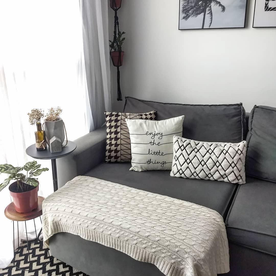 sofa cinza com elementos decorativos neutros