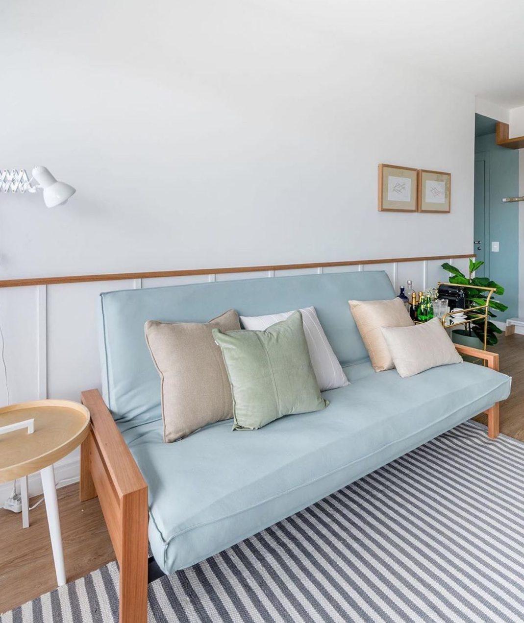 sofa cama azul claro em sala de tons pasteis