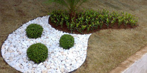 jardim com pedra portuguesa branca e arbustos