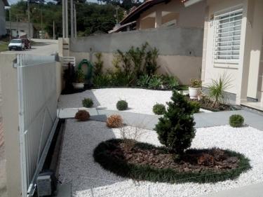 brita branca em jardim de casa