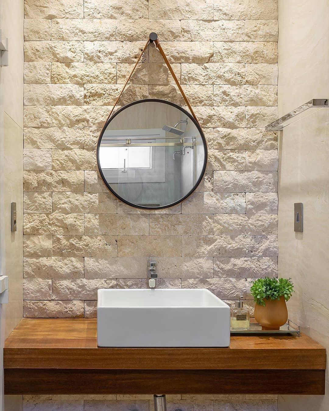 espelho redondo adnet no banheiro com revestimento de pedra