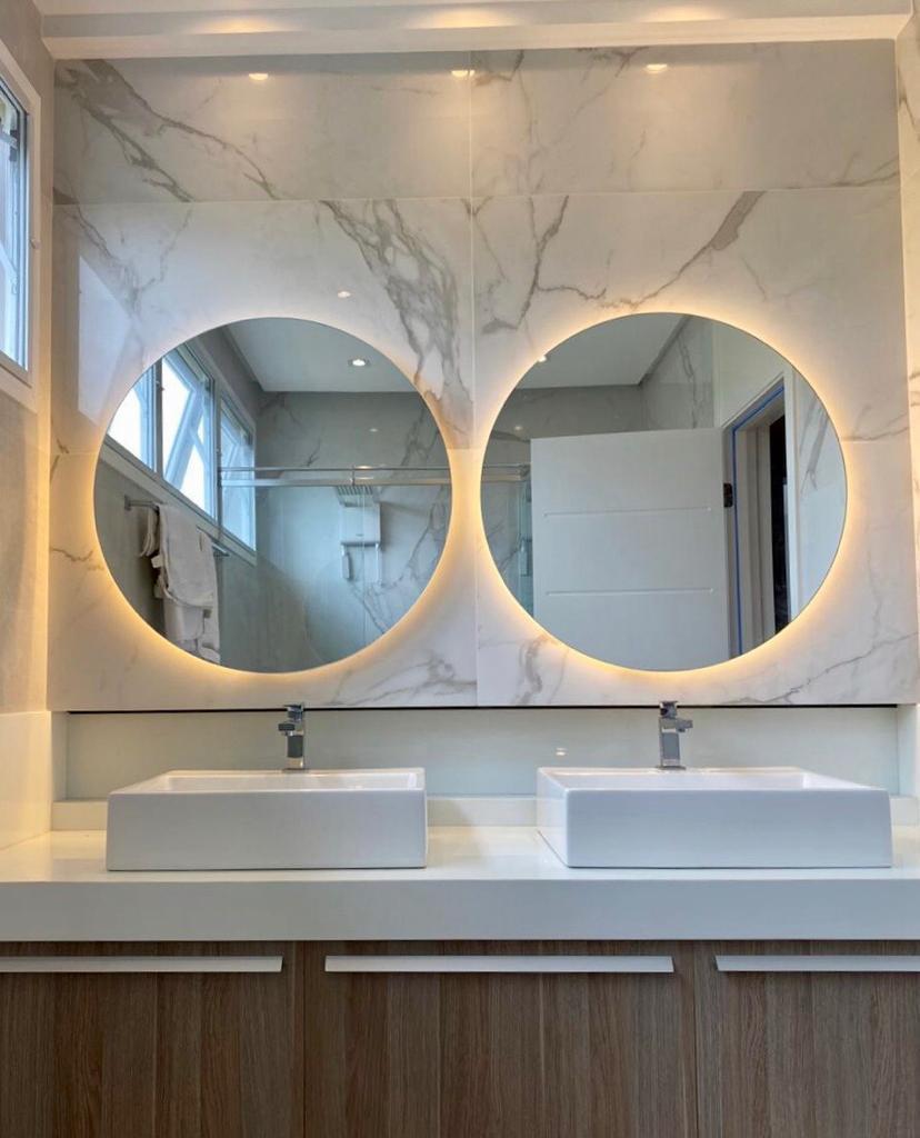 espelho redondo iluminado no banheiro com revestimento de mármore