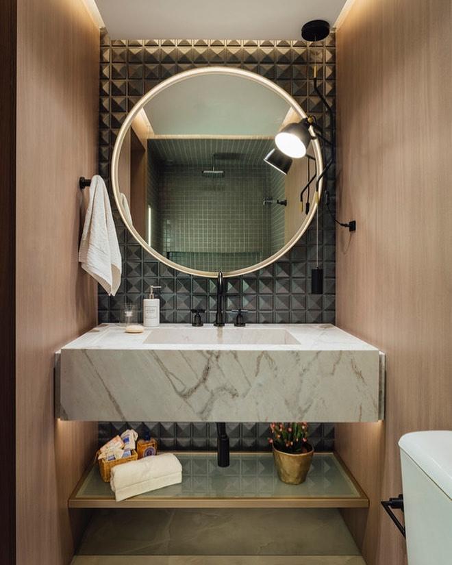 espelho redondo grande iluminado em banheiro moderno