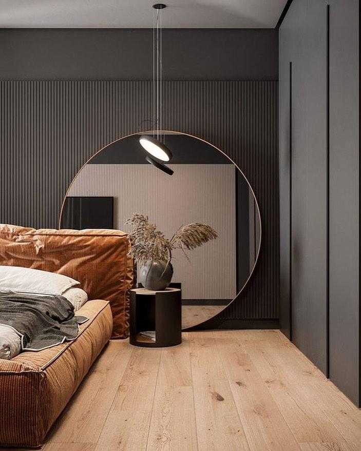 espelho redondo grande no quarto como cabeceira