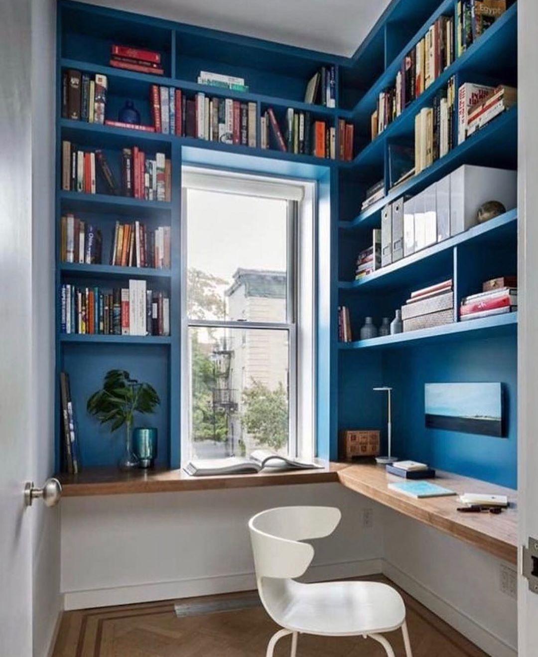 home office com prateleiras e parede em azul