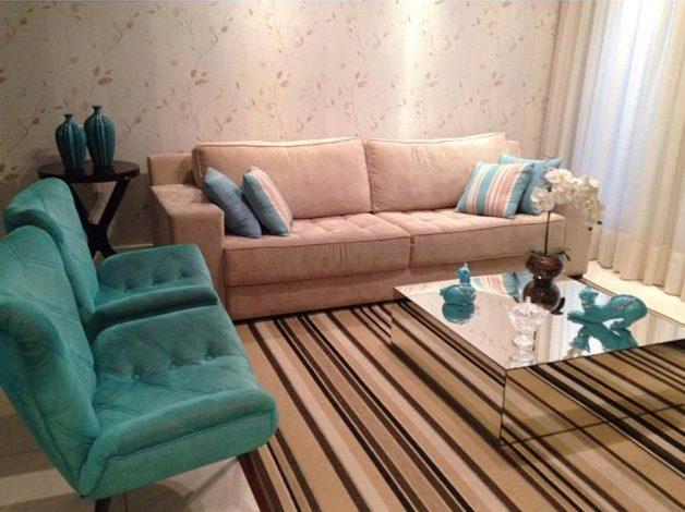 sala em tons neutros e detalhes em azul turquesa com mesa de centro espelhada