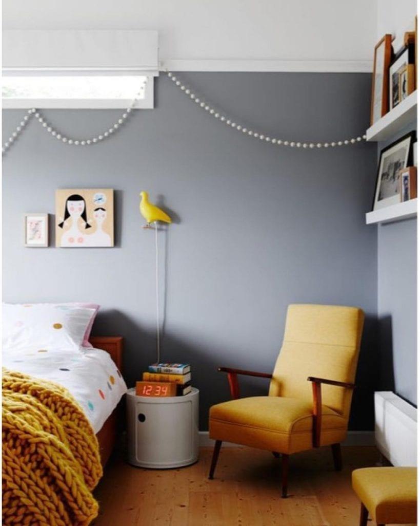 quarto inantil com parede cinza e poltrona amarelo mostarda