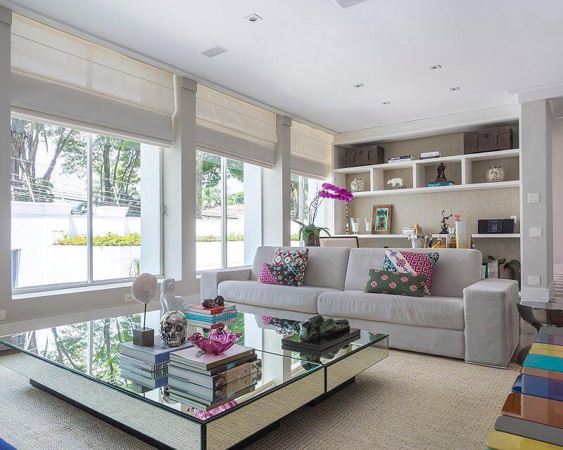 sala de estar ampla e iluminada com mesa de centro espelhada e detalhes em rosa