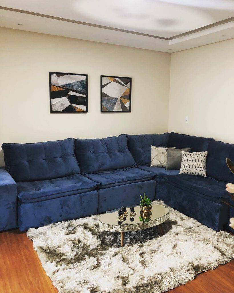 sala com sofá azul e mesa de centro espelhada oval