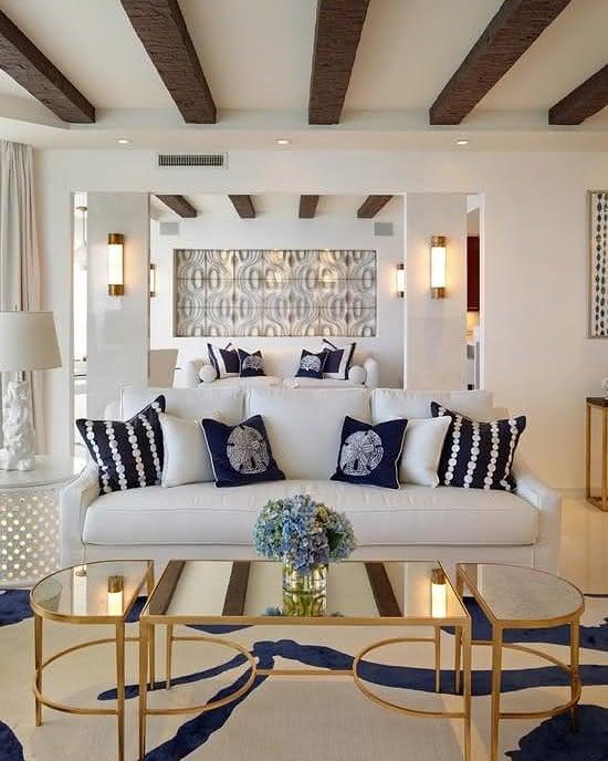 sala de casa de praia com mesa de centro dourada e espelho em cima