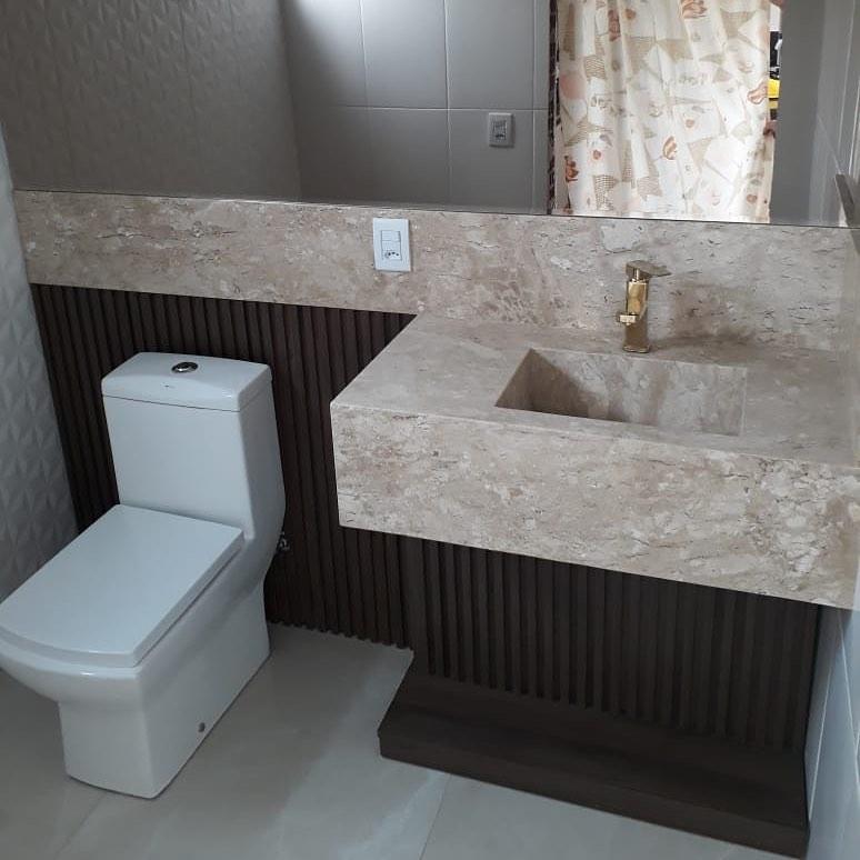 lavabo com bancada esculpida em marmore travertino e combinação com marrom escuro