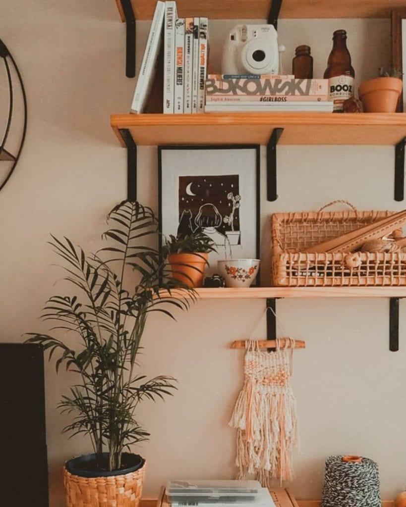 prateleiras com objetos decorativos, planta e tapeçaria na parede