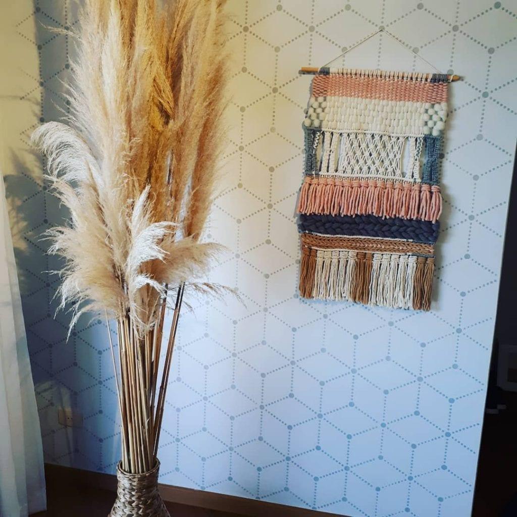 cantinho boho com tapeçaria e vaso de galhos secos