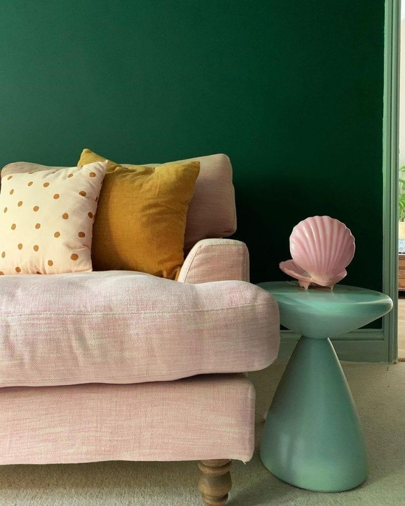sofá com almofada mostarda e parede verde escuro