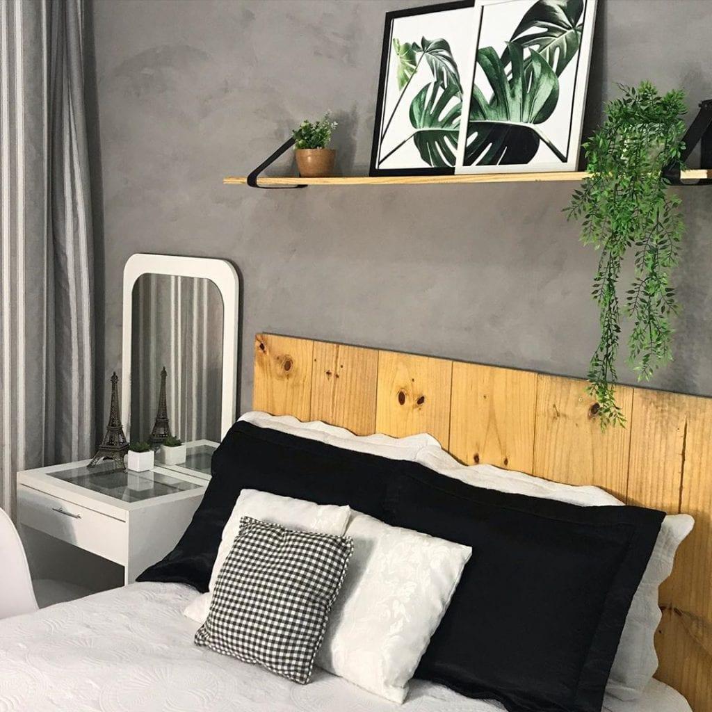 cabeceira de madeira em quarto com parede de cimento queimado