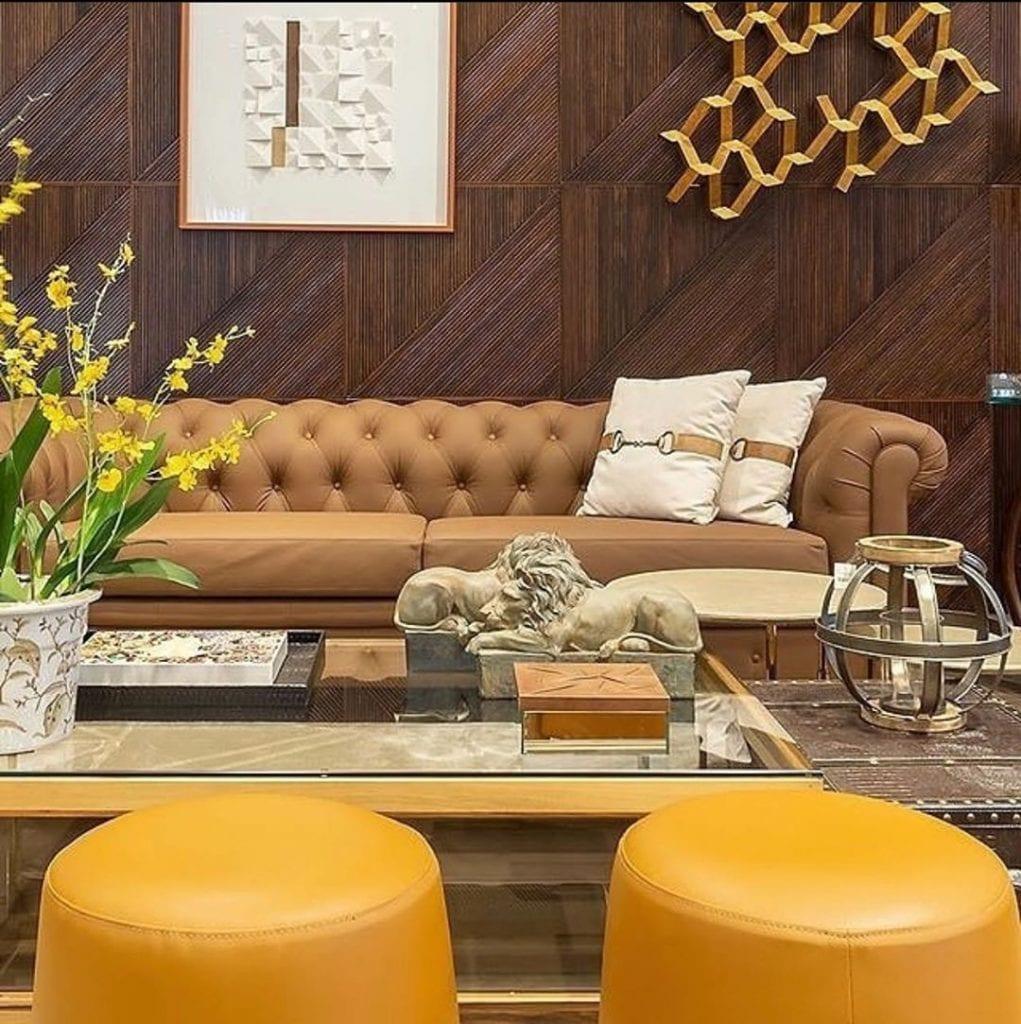 sala em tons de marrom e amarelo com sofa chesterfield de couro