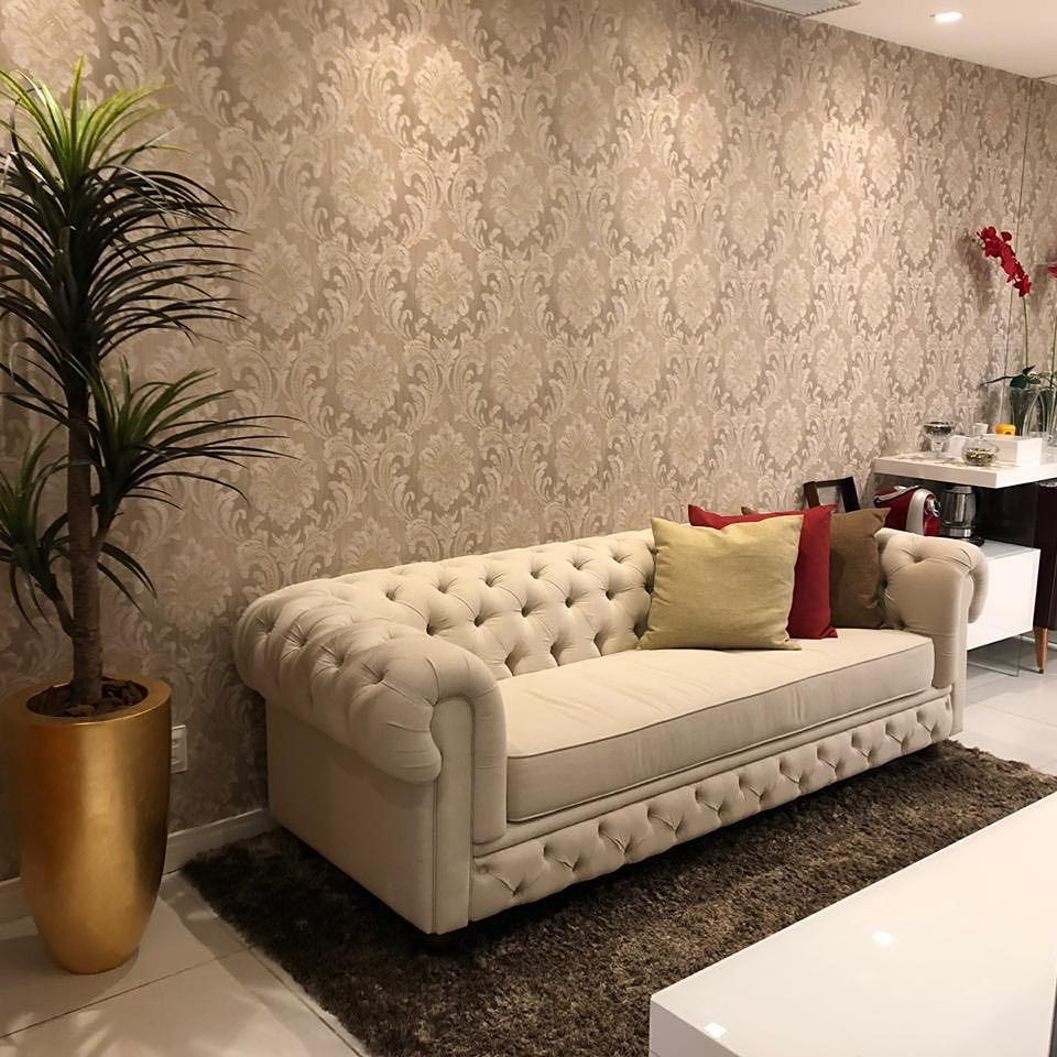 sofa chesterfiel em veludo bege claro em sala com papel de parede