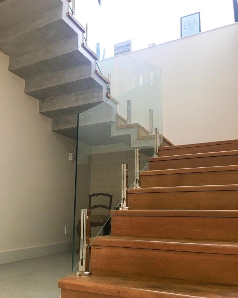 escada de madeira com guarda-corpo de vidro e cimento queimado