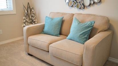 Foto de um sofá bege com almofadas azuis em uma sala. Vemos um quadro, planta e janela ao lado. Imagem ilustrativa para texto mistura para limpar sofá.